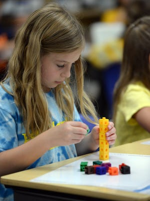 Chloe Tebon, a second-grade student at Bay Harbor Elementary School in Suamico, uses interlocking blocks to work on a math problem in Melissa Madigan's classroom on Wednesday.