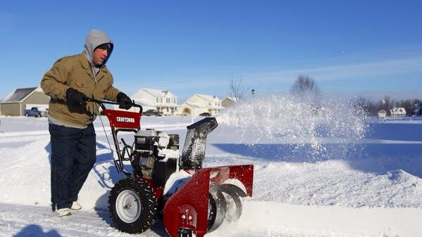 Mark Petroske, of Hilton, clears snow from last nights storm from his driveway.