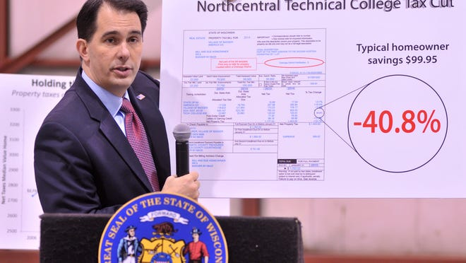 Gov. Scott Walker holds up a property tax sample Wednesday during his speech at the Wausau Downtown Airport.