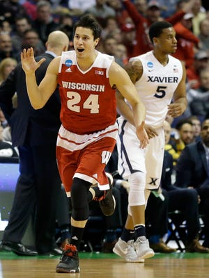 Wisconsin's Bronson Koenig, left, celebrates as he runs past Xavier's Trevon Bluiett after sinking a 3-point basket during the first half in a second-round men's college basketball game in the NCAA Tournament, Sunday, March 20, 2016, in St. Louis. (AP Photo/Jeff Roberson)