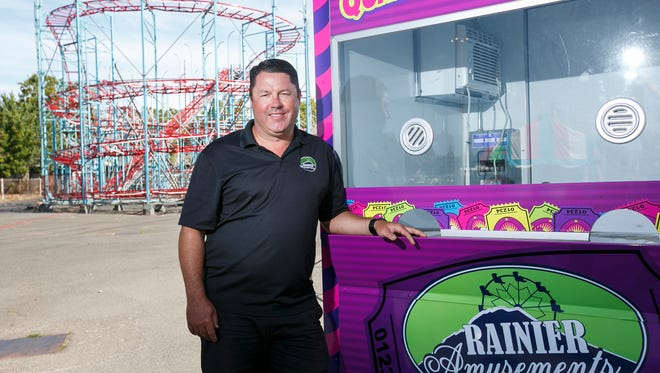 Mitch Hoss, who owns Rainier Amusements with his wife Crystal, stands by one of the company's ticket booths as they prepare to open the carnival for the state fair on Friday. Behind Hoss is the fair's first roller coaster since 1967.