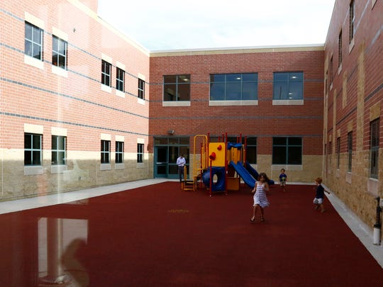 Kids play in a primary-colored playground at GD Jones Elementary School in Wausau.