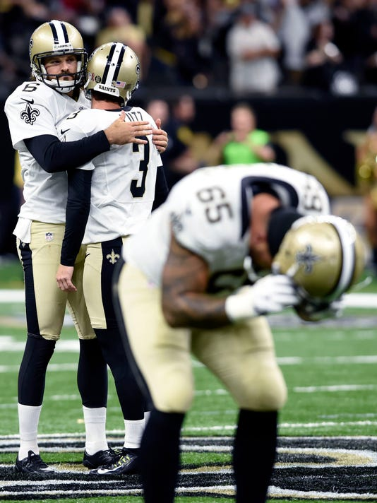 New Orleans Saints kicker Wil Lutz (3) reacts with holder Thomas Morstead (6) after missing a potential game winning field goal with no time left in the second half of an NFL football game against the Oakland Raiders in New Orleans, Sunday, Sept. 11, 2016.  Foreground is guard Senio Kelemete (65). The Raiders won 35-34.(AP Photo/Bill Feig)