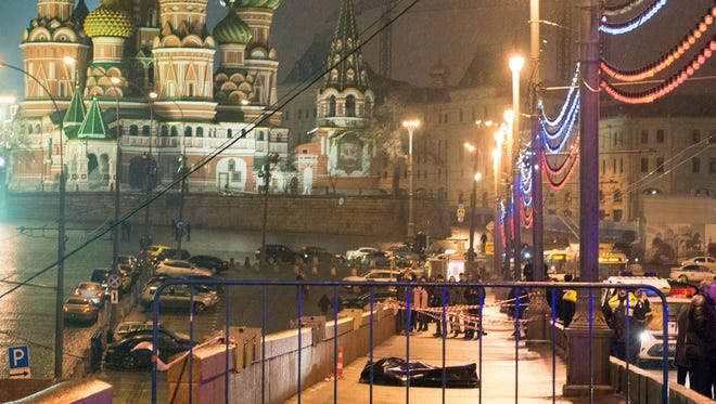 The body of Russian opposition leader Boris Nemtsov is covered with plastic lies on Moskvoretsky bridge near St. Basil cathedral (background) in central Moscow on Feb.28, 2015.
