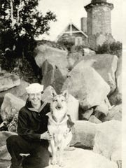 Gert Wellisch poses with her dog, Sandy, in front of the Sand Island lighthouse.