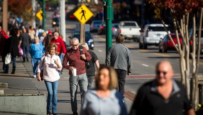 Visitors walk along the Parkway in Gatlinburg on Tuesday, Nov. 28, 2017, the one year anniversary of the deadly wildfires that swept through the town.