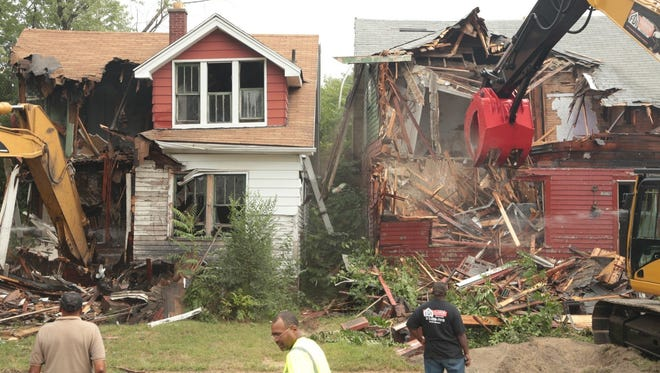 Demolition crews tear down abandoned houses on Turner Street in Detroit on August 26, 2013, following a news conference to kick off the state's largest residential blight removal effort.