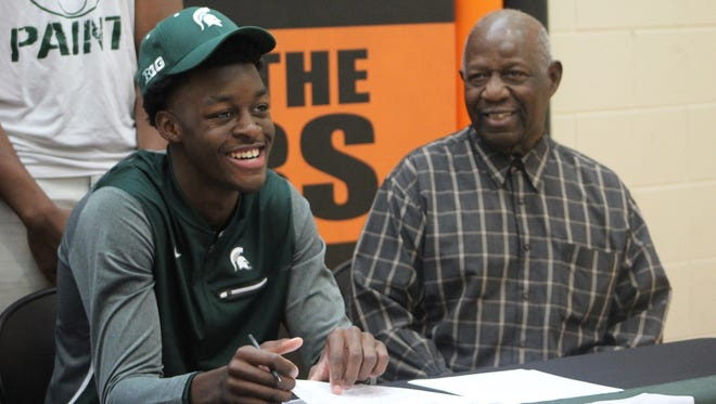 Belleville High School senior Gabe Brown signs his letter of intent Nov. 8, 2017 to attend Michigan State University on a full-ride basketball scholarship. The four-star recruit is pictured with his grandfather, Clinton Brown, who has helped raise him since his father, Charles Brown, died in May of 2016.