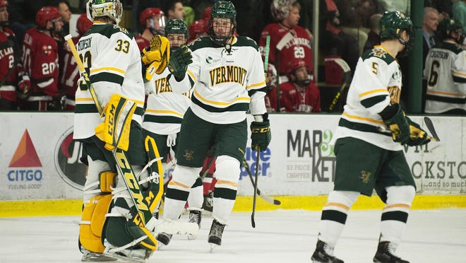 Catamount defenseman Ori Abramson (27) and goalie Packy Munson celebrate a goal during the men's hockey game between the St. Lawrence Saints and the Vermont Catamounts at Gutterson Fieldhouse earlier this month.