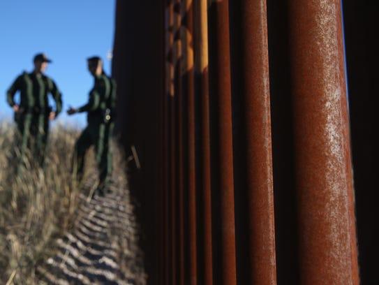 U.S. Border Patrol agents talk next to the United States-Mexico