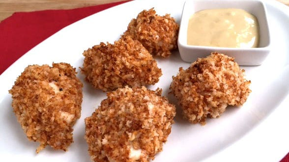 Panko crumbs give oven-fried chicken nuggets crunch. Serve them with a maple-Dijon dip.
