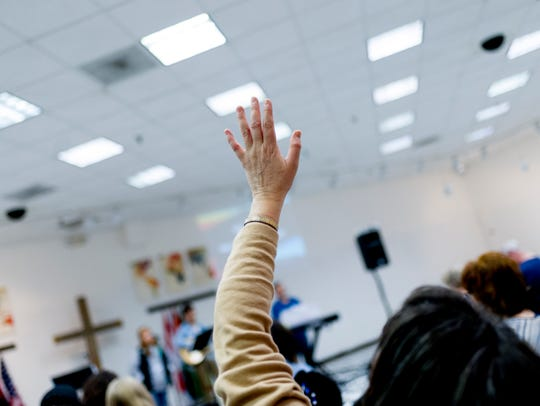 A worshipper waves her hand during a song at the monthly