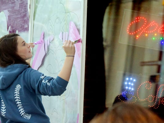 Dallastown High School sophomore Cara Druck and classmates paint a storefront New Grounds Roasting Company on West Market St. Tuesday, Oct. 13, 2015. About 80 Dallastown students painted 23 storefront windows along the Halloween parade route. Co-sponsor Maple Donuts asked that the artwork reflect a doughnut theme. The York Halloween Parade is Sunday, October 25 at 2 p.m. Bill Kalina - bkalina@yorkdispatch.com