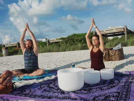 Isabel Silva and Johnna Svoboda do yoga on Barefoot Beach on Sunday evenings.