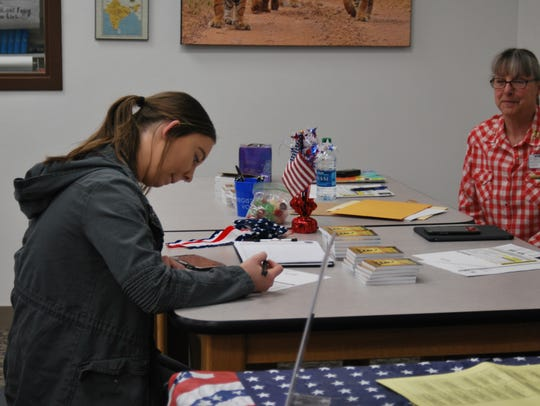 Aztec High School junior Rachel Brown registers to vote as community volunteer Neva Meeks looks on during a voter registration drive on Monday in the school's library.