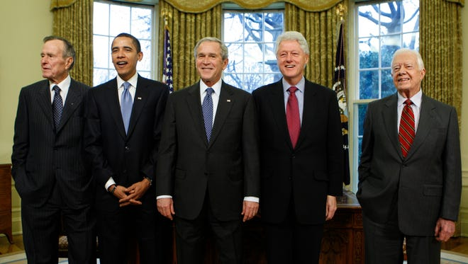President George W. Bush poses with President-elect Barack Obama and former presidents George H.W. Bush, Bill Clinton and Jimmy Carter, on Jan. 7, 2009 in the Oval Office of the White House.