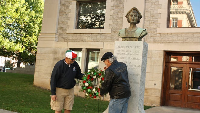 Mark Dozoretz, left, of Binghamton, and Pat Cerrra, of Johnson City, place a wreath under a statue of Christopher Columbus in downtown Binghamton. Dozoretz and Cerra are the presidents of the Binghamton and Endicott branches of the Sons of Italy, respectively.