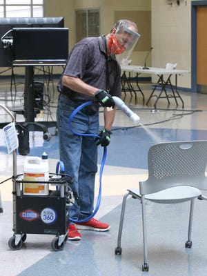 Mark Young, operations supervisor with Canton City Schools, disinfects chairs at the McKinley High School downtown campus in Canton on Tuesday. The district announced that students will start the school year learning from home. They will return to classes Sept. 8.