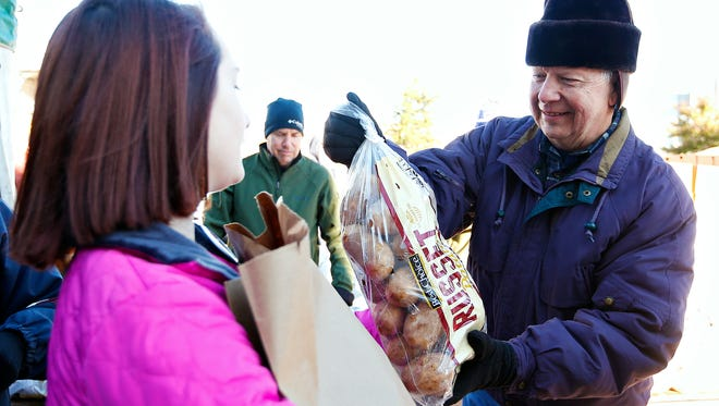 Tom Flanagan, a volunteer with United Methodist Church, hands over a sack of potatoes to a fellow volunteer during a Thanksgiving meal distribution event organized by Crosslines and held at Central Assembly Church in Springfield, Mo. on Nov. 19, 2016.