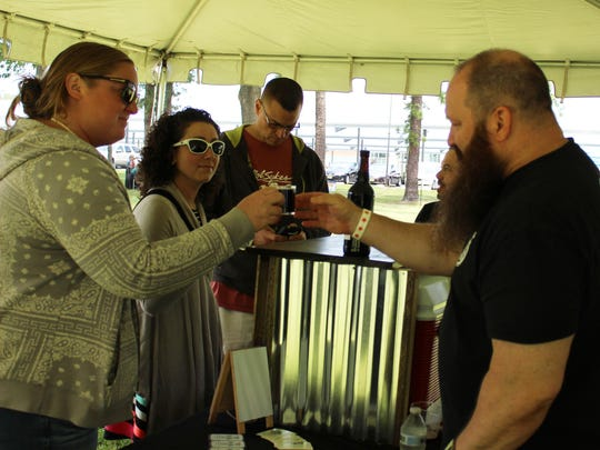 John Colbert of Tomfoolery Brewery hands Jenn Dolan a glass filled with one of the brewery's specialty beers.
