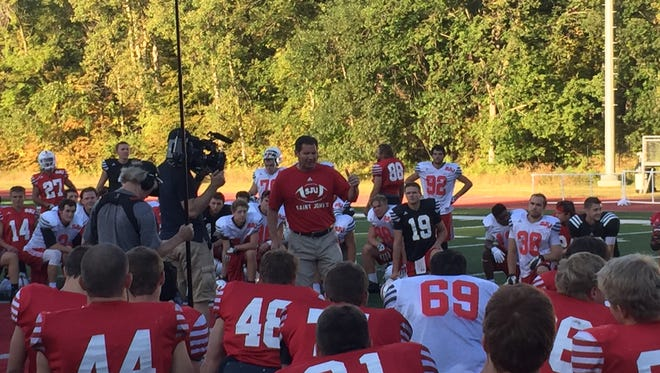 An ESPN camera crew films St. John's head coach Gary Fasching as he talks to the team after practice Tuesday at Clemens Stadium.
