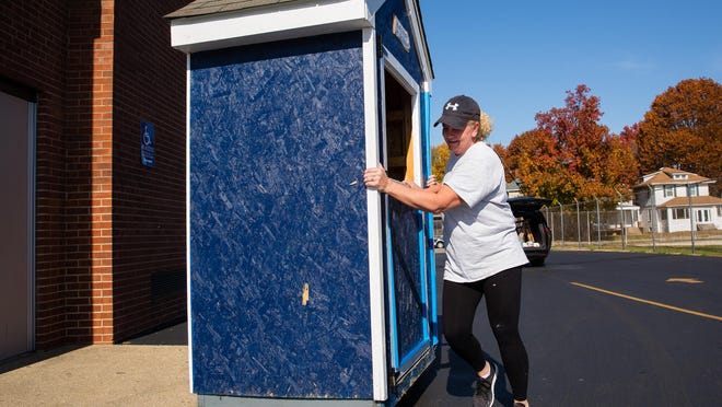 Lynn Ehmen, a volunteer with the Springfield Families Helping Families group, helps move a micropantry into a location that can been monitored by security cameras at Lanphier High School after a recent spate of vandalism to it.