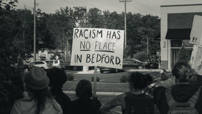 """This image, which reads """"Racism has no place in Bedford,"""" appears with the Change.org petition calling for Gov. Gretchen Whitmer to remove Trustee Todd Bruning from the Bedford Public Schools Board of Education."""