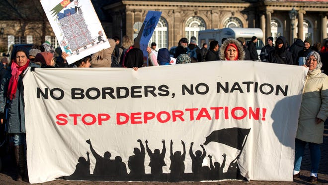 """Protestors holding a banner that reads """"No Borders, No Nation, Stop Deportation!"""" during a protest against the deportation of asylum seekers from Germany, in Dresden, Germany, Saturday Dec. 17, 2016."""