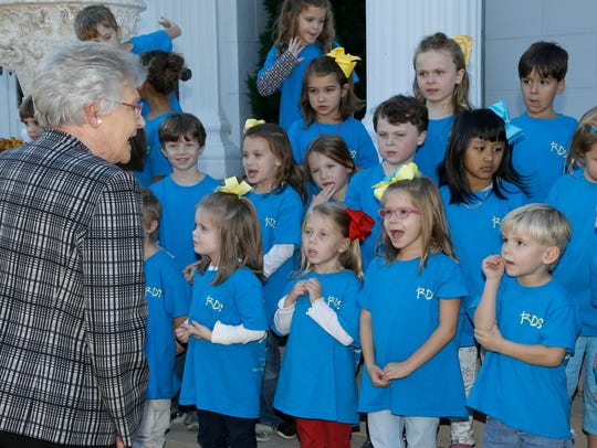 Gov. Kay Ivey sings with a children's choir during