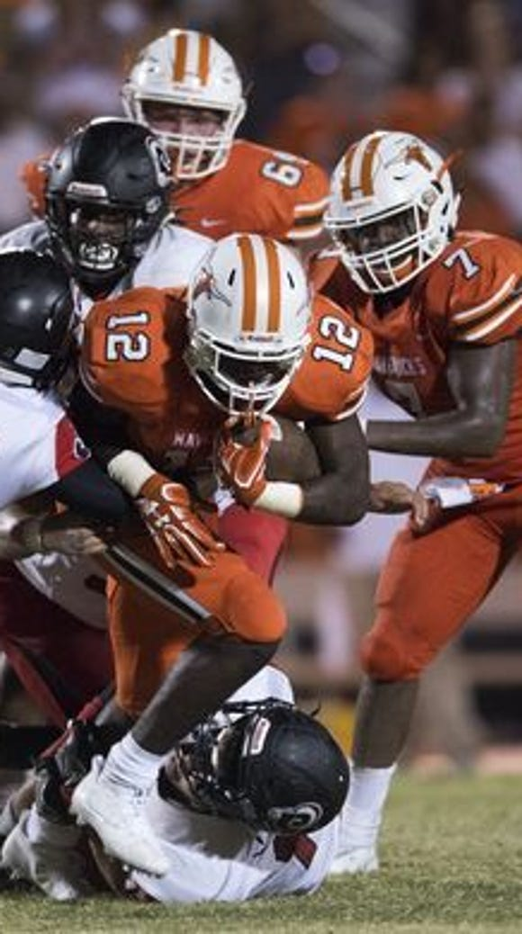 Mauldin's Jason Branham (12) is brought down by the