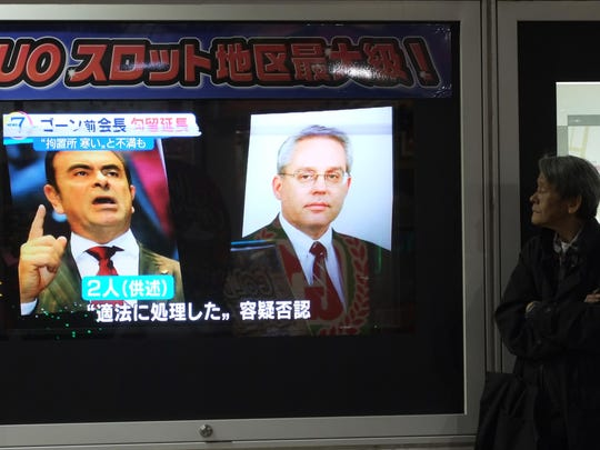 A man looks at a television showing a news programme featuring former Nissan chief Carlos Ghosn, left, and representative director Greg Kelly in Tokyo on November 30, 2018. A Tokyo court on November 30 extended the detention of former Nissan chief Carlos Ghosn, local media said, after his arrest on allegations of financial misconduct that have shaken the auto industry.