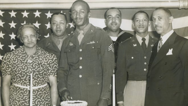 From left, Mrs. Pearl Robinson, general chairman of the dinner committee at Ebenezer Baptist Church, stands with Sgt. Nelson E. Hancock, Sgt. Nathaniel Morgan, Coxswain James A. Green, First Lieut. Walter M. Patrice and the Rev. Thomas J. Jenkins, pastor of the church.