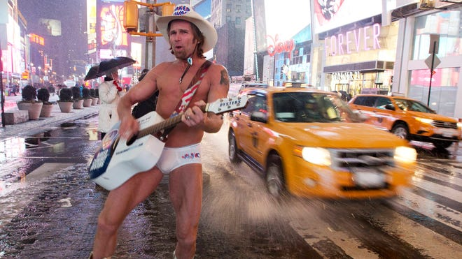 "Robert Burck, aka the ""Naked Cowboy,"" performs in Times Square as it snows on  Feb. 8, 2013, in New York."