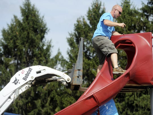 Jason Plotkin — York Daily Record/Sunday News Andy Willow of Willow Playworks, helps make adjustment to the new playground at Memorial Park on Friday.