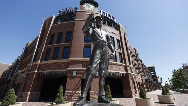 """The bronze statue entitled """"The Player,"""" by sculptor George Lundeen, stands in front of the main gate of Coors Field, home of the  Colorado Rockies, on Tuesday. MLB was waiting for the players' union to respond to whether it will agree to health protocols for a 60-game regular-season slate and if players will report for training camp by July 1."""