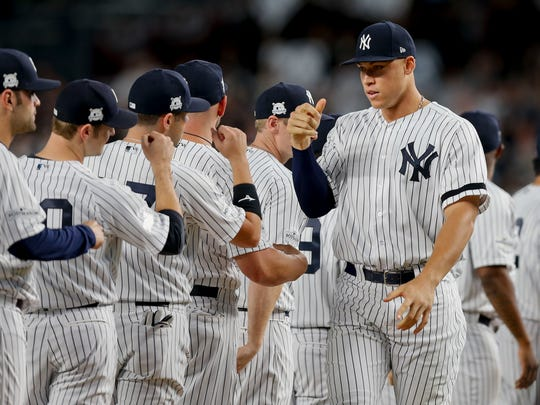 Yankees' Aaron Judge, right, greeting teammates before playing against the Cleveland Indians in the ALDS.