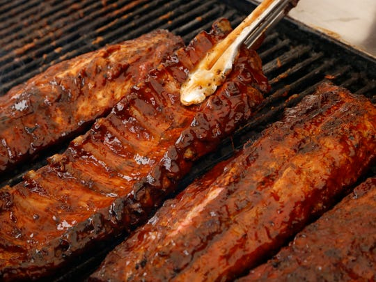 Ronald Moton Sr., the owner of The King of Bar-B-Que Ribs, flips his Texas style rib slabs on a grill in the parking lot of the Lowe's Home Improvement in Ontario.