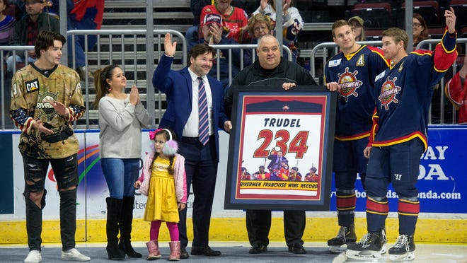 Peoria Rivermen head coach Jean-Guy Trudel waves to the crowd during a ceremony honoring his franchise coaching victories record, while co-owner Bart Rogers presents him with a special jersey and captain Alec Hagaman (far right) looks on before a game against Quad City on Saturday, Nov. 23, 2019.