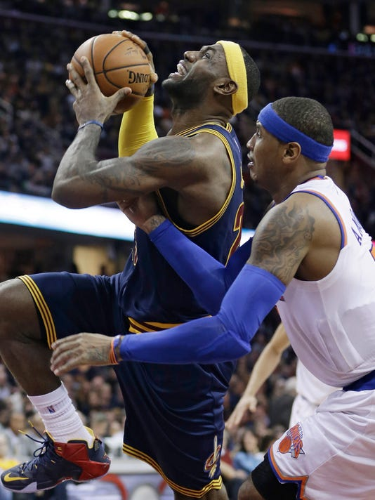 New York Knicks' Carmelo Anthony, right, fouls Cleveland Cavaliers' LeBron James (23) during the fourth quarter of an NBA basketball game Thursday, Oct. 30, 2014, in Cleveland. The Knicks defeated the Cavaliers 95-90. (AP Photo/Tony Dejak)