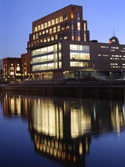Lights of the AF Group headquarters reflect on the Grand River in this 2011 file photo. The insurance company, formerly known as Accident Fund, rehabilitated a former power plant to create the office complex.