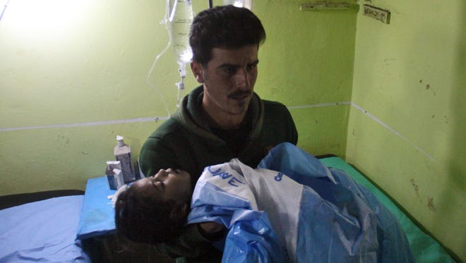 A man holds an unconscious Syrian child at a hospital in Khan Sheikhoun, a rebel-held town in Idlib province, following a suspected toxic gas attack on April 4, 2017.