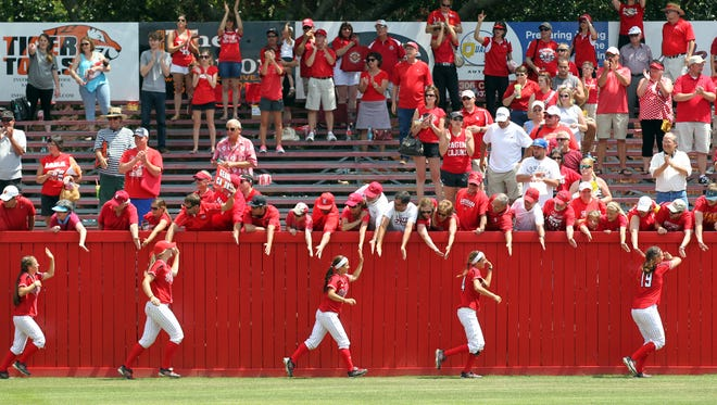 UL players high-five fans along the outfield wall after defeating Texas 10-1 during an NCAA Regional softball tournament game Sunday at Lamson Park in Lafayette.