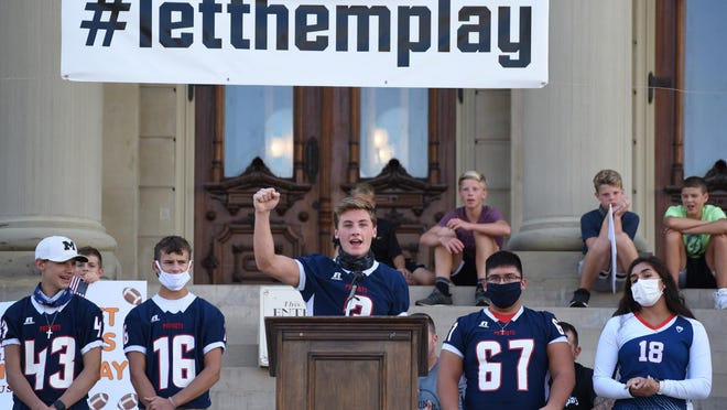 Britton Deerfield high school quarterback junior Nico Johnson speaks at the Michigan State Capitol Friday evening. Behind him are teammates Carson Johnson (43), Mason Mueller (16), Dominic Arriaga (67) and volleyball player Madelina Arriaga.
