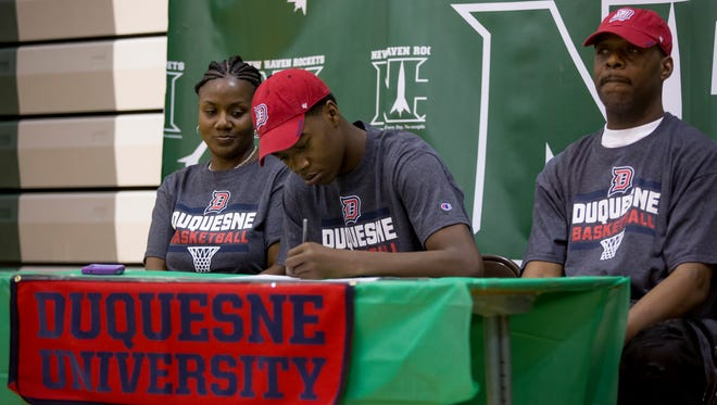 Eric Williams Jr. signs with Duquesne University while sitting with his parents, Clarice Williams and Eric Williams Sr. Tuesday, April 25, 2017 at New Haven High School.
