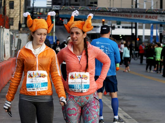 Tristyn Eppley of Loveland, left, and Katie Peace of Kings Mills sport their turkey hats before running in The Western and Southern 106th Thanksgiving Day Race Thursday November 26,  2015.