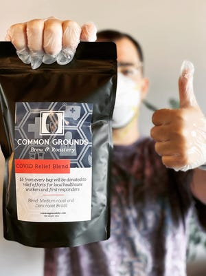 "Christopher Zaskey, a Common Grounds barista, holds up a bag of the shop's ""COVID Relief Blend."""