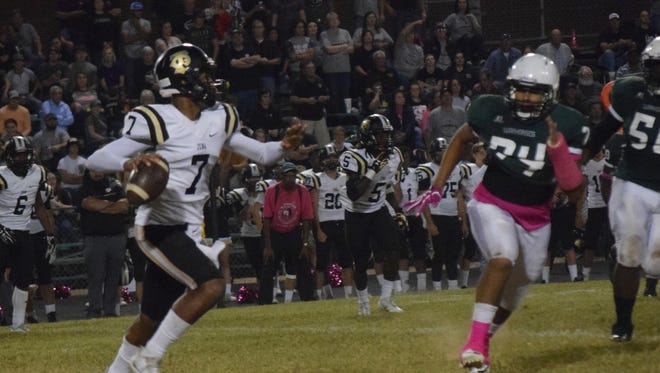Jena's Lamar Farris (7, left) looks to pass against Peabody defender Wayne Compton (74, right) during a game last season.