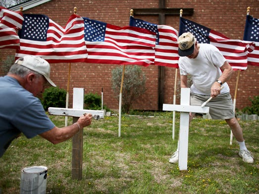 Bob Gordon, left, and Bob Butler paint crosses they placed in front of 16 American flags as they build a memorial in front of Central Christian Disciples of Christ church for the shooting victims at Fort Hood in Texas. Iraq War veteran Ivan Lopez claimed three lives and wounded 16 people before taking his own life, authorities say.