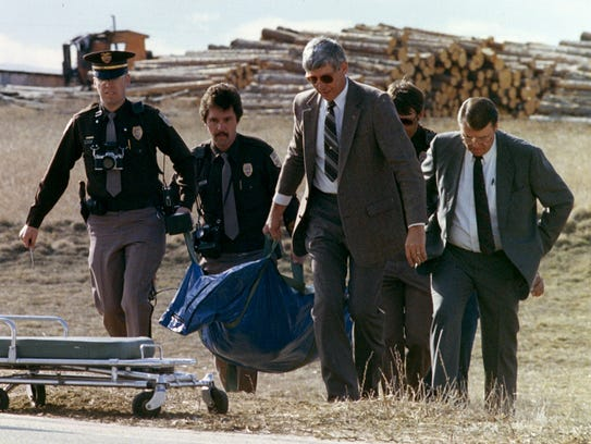 Police investigators move the body of Peggy Lee Hettrick