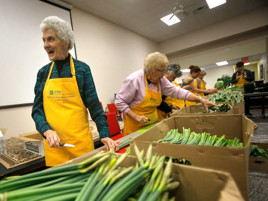 Joann Sattler, left, joins dozens of other volunteers in preparing daffodil orders March 17 at the First Presbyterian Church in Farmington.